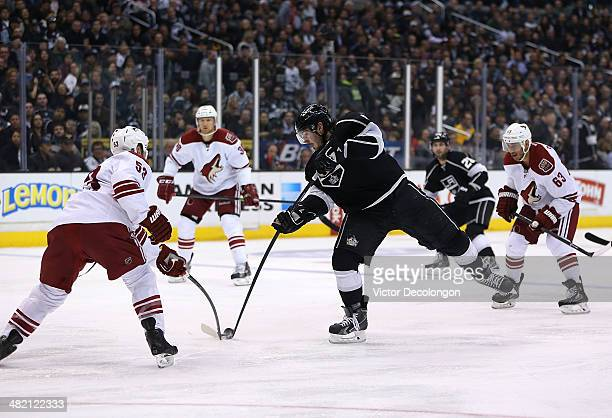 Derek Morris of the Phoenix Coyotes gets a stick on the puck as Drew Doughty of the Los Angeles Kings tries for a shot on goal in the second period...