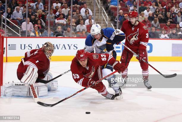 Derek Morris of the Phoenix Coyotes is checked by TJ Oshie of the St Louis Blues as he attempts to clear the puck during the NHL game at Jobingcom...