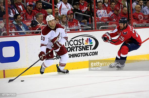 Derek Morris of the Phoenix Coyotes passes the puck in front of Jason Chimera of the Washington Capitals at Verizon Center on March 8, 2014 in...
