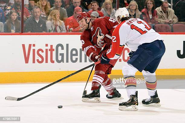 Derek Morris of the Phoenix Coyotes passes the puck under the stick of Jimmy Hayes of the Florida Panthers during the first period at Jobing.com...