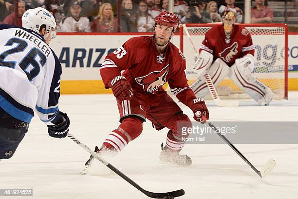 Derek Morris of the Phoenix Coyotes skates back into his own zone while defended by Blake Wheeler of the Winnipeg Jets at Jobing.com Arena on April...
