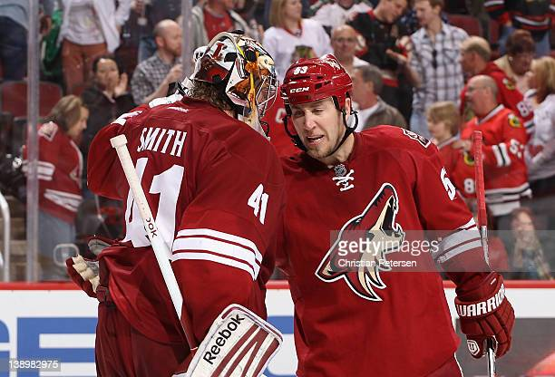Derek Morris of the Phoenix Coyotes skates over to congratulate goaltender Mike Smith after defeating the Chicago Blackhawks in the NHL game at...