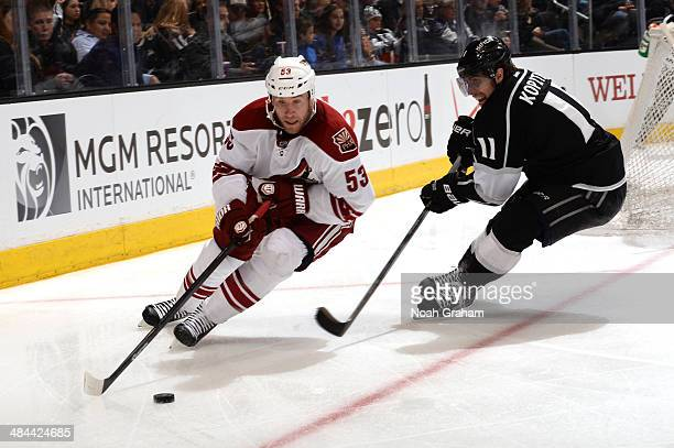 Derek Morris of the Phoenix Coyotes skates with the puck against Anze Kopitar of the Los Angeles Kings at Staples Center on April 2, 2014 in Los...