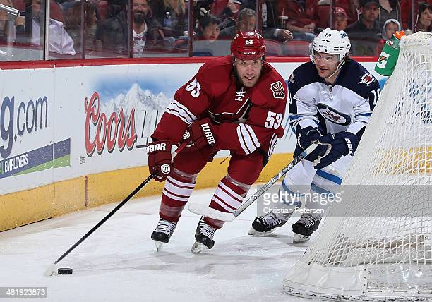 Derek Morris of the Phoenix Coyotes skates with the puck past Jim Slater of the Winnipeg Jets during the second of the NHL game at Jobing.com Arena...
