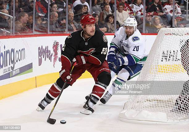 Derek Morris of the Phoenix Coyotes skates with the puck past Christopher Higgins of the Vancouver Canucks during the NHL game at Jobingcom Arena on...