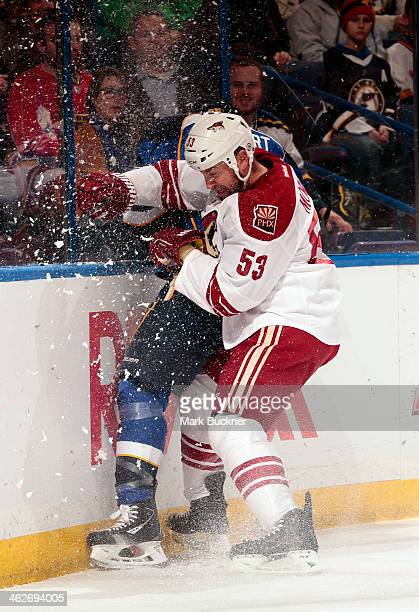 Derek Morris of the Phoenix Coyotes slams Chris Stewart of the St Louis Blues into the boards during an NHL game on January 14 2014 at Scottrade...