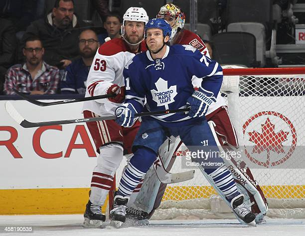 Derek Morris of the Phoenix Coyotes tries to keep David Clarkson of the Toronto Maple Leafs in check during an NHL game at the Air Canada Centre on...