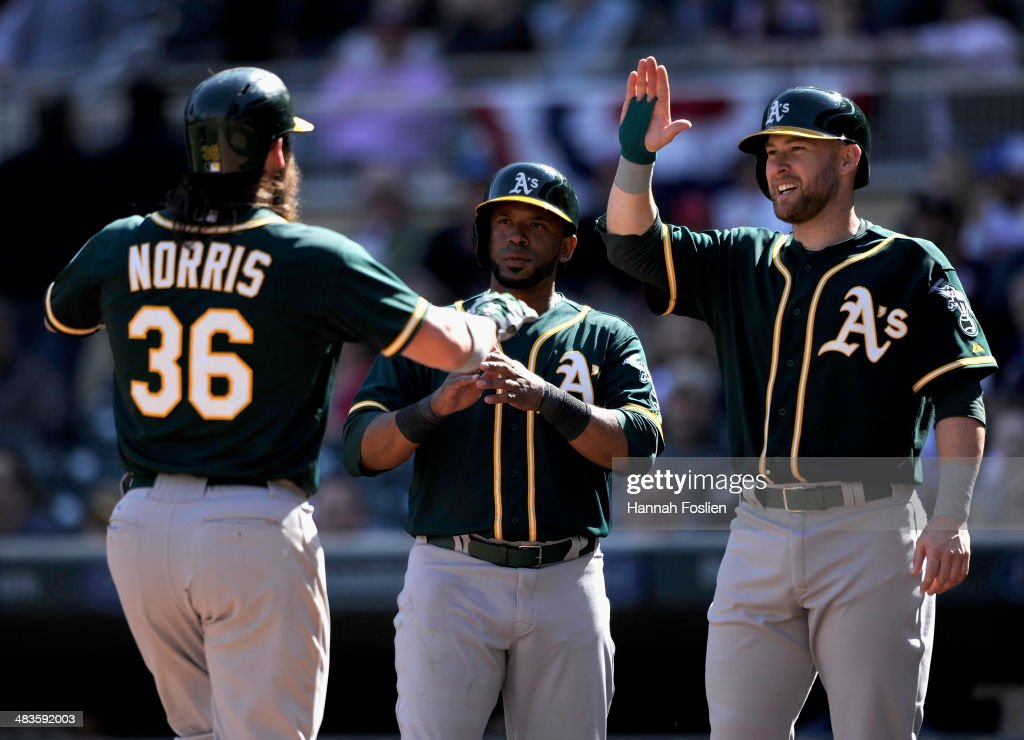 Derek Norris #36, Alberto Callaspo #18 and Daric Barton #10 of the Oakland Athletics celebrate a three run home run by Norris during the tenth inning of the game on April 9, 2014 at Target Field in Minneapolis, Minnesota. The Athletics defeated the Twins 7-4 in eleven innings.