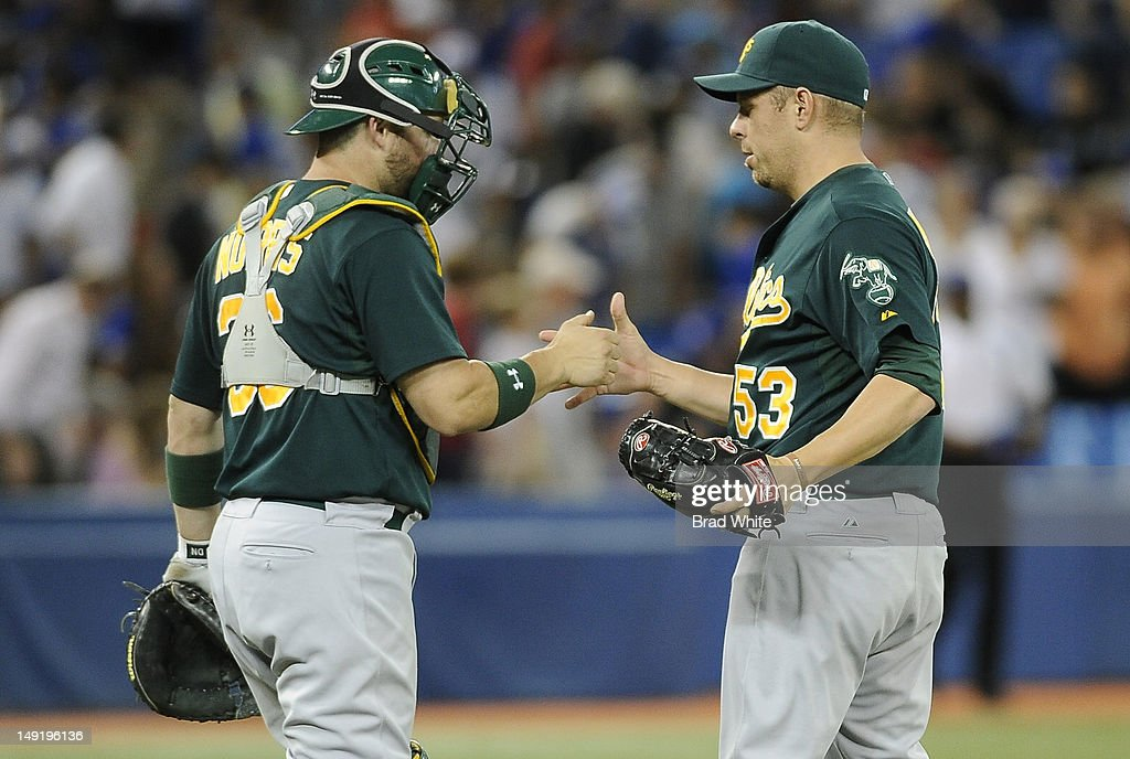 Derek Norris #36 and Jim Miller #53 of the Oakland Athletics celebrate the teams win over the Toronto Blue Jays during MLB game action July 24, 2012 at Rogers Centre in Toronto, Ontario, Canada.