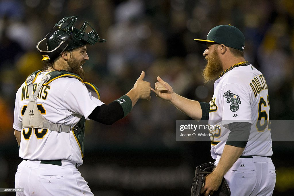 Derek Norris #36 of the Oakland Athletics celebrates with Sean Doolittle #62 after the game against the Tampa Bay Rays at O.co Coliseum on August 5, 2014 in Oakland, California. The Oakland Athletics defeated the Tampa Bay Rays 3-0.