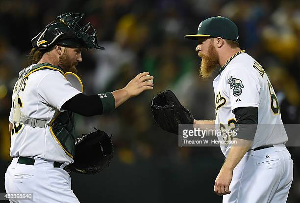 Derek Norris of the Oakland Athletics gives the game ball to pitcher Sean Doolittle after the Athletics defeated the Minnesota Twins 65 at Oco...