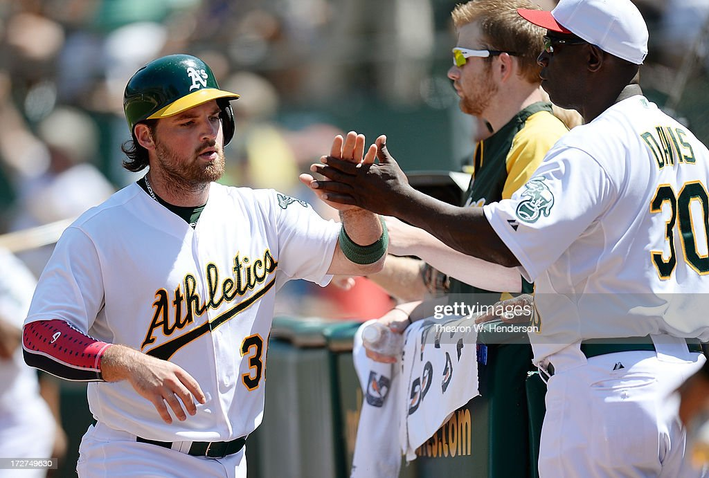 Derek Norris #36 of the Oakland Athletics is congratulated by coach Chili Davis #30 after Norris scored on a past ball in the seventh inning against the Chicago Cubs at O.co Coliseum on July 4, 2013 in Oakland, California.