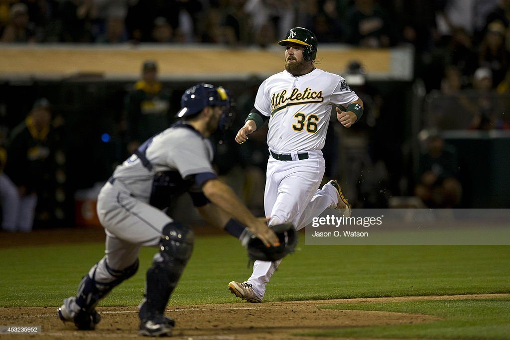 Derek Norris #36 of the Oakland Athletics scores a run past Curt Casali #59 of the Tampa Bay Rays during the sixth inning at O.co Coliseum on August 5, 2014 in Oakland, California.