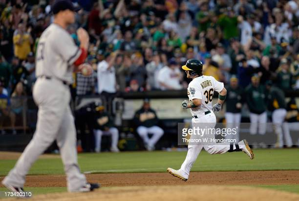 Derek Norris of the Oakland Athletics trots around the bases after hitting a solo home run as pitcher Jon Lester of the Boston Red Sox looks on with...