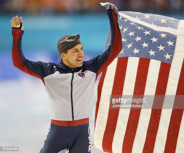 Derek Parra jubilates with the US flag after setting a new world record in 14395 and winning the men's 1500m speedskating race at the Utah Olympic...