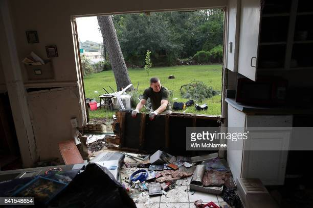 Derek Pelt removes a portion of his friend Bryan Parson's home while helping to remove damage caused by flooding brought on by Hurricane Harvey...