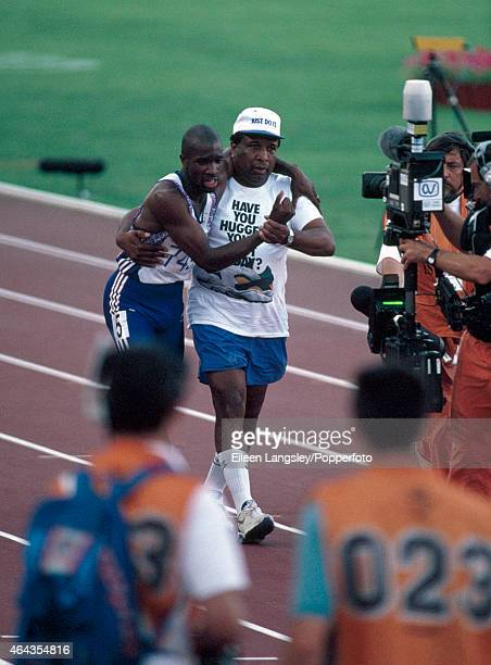 Derek Redmond of Great Britain is aided by his father Jim Redmond to complete a full lap of the track after tearing his hamstring in the semifinal of...