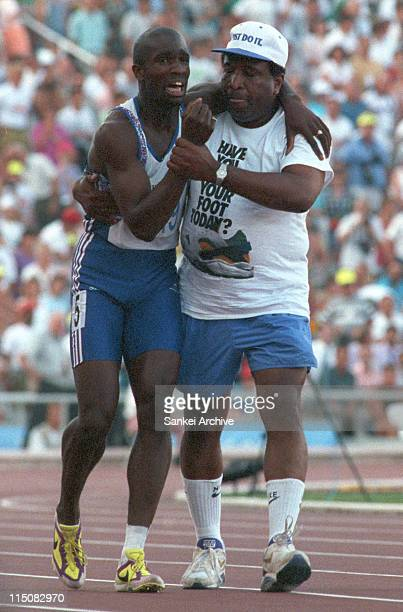 Derek Redmond of Great Britain is helped towards the finish line by his father after suffering an injury in the Men's 400m semifinal during the...