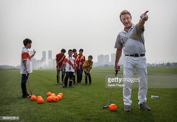 Derek Reid Director of Polo Operations right gestures as he instructs young Chinese players from the Junior Polo Programme during stick and ball...
