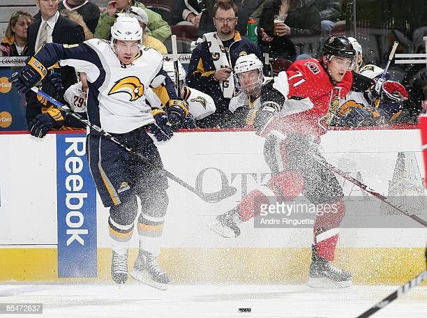 Derek Roy of the Buffalo Sabres keeps control of the puck as he avoids a check by Nick Foligno of the Ottawa Senators at Scotiabank Place March 17...
