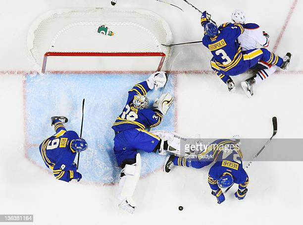 Derek Roy Ryan Miller Robyn Regehr and Jordan Leopold of the Buffalo Sabres battle Taylor Hall of the Edmonton Oilers to keep the puck out of the net...