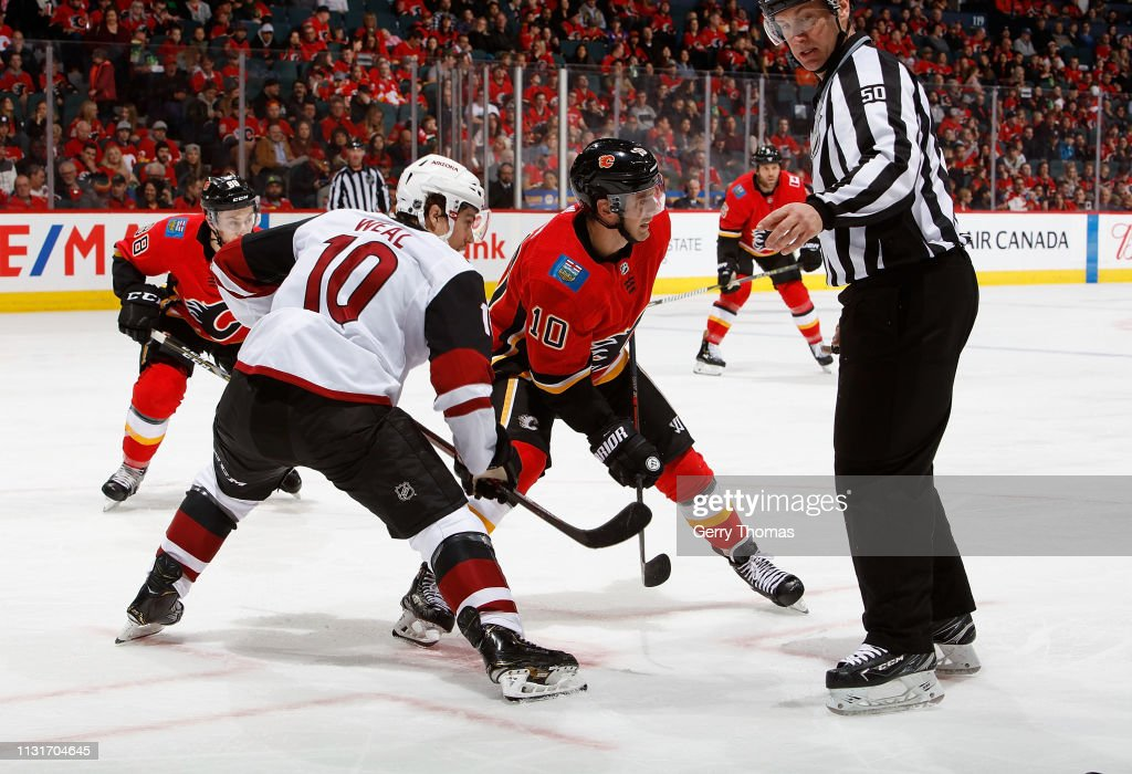 Derek Ryan of the Calgary Flames faces off against Jordan Weal the