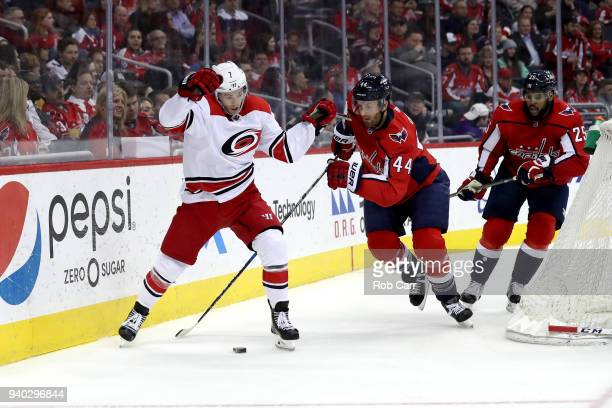Derek Ryan of the Carolina Hurricanes and Brooks Orpik of the Washington Capitals go after the puck in the third period at Capital One Arena on March...