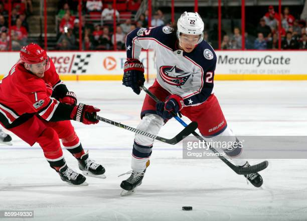 Derek Ryan of the Carolina Hurricanes attempts to poke the puck away from Sonny Milano of the Columbus Blue Jackets during an NHL game on October 10...