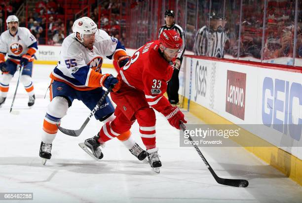 Derek Ryan of the Carolina Hurricanes controls the puck away from Johnny Boychuk of the New York Islanders during an NHL game on April 6 2017 at PNC...