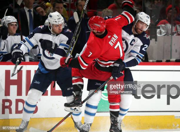 Derek Ryan of the Carolina Hurricanes is absorbs hits from Ben Chiarot and Blake Wheeler of the Winnipeg Jets during an NHL game on March 4 2018 at...