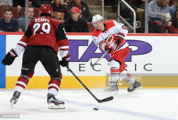 Derek Ryan of the Carolina Hurricanes passes the puck as Mario Kempe of the Arizona Coyotes defends during the second period at Gila River Arena on...