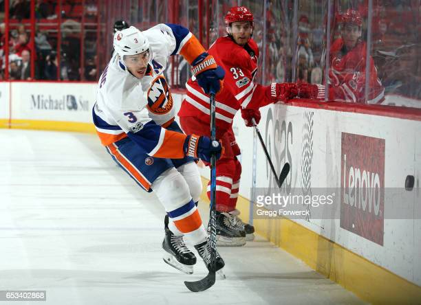 Derek Ryan of the Carolina Hurricanes watches as Travis Hamonic of the New York Islanders chips the puck into the neutral zone during an NHL game on...