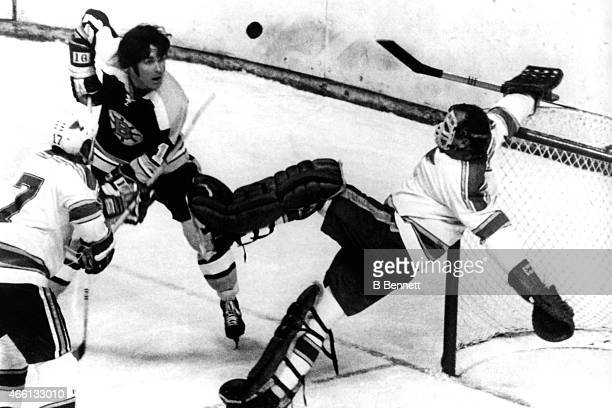 Derek Sanderson of the Boston Bruins looks surprised as goalie Glenn Hall of the St Louis Blues makes the kick save as he holds onto the net as his...
