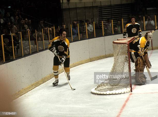 Derek Sanderson of the Boston Bruins skates with the puck around the net as goalie Gerry Cheevers looks on during their NHL game in January, 1972.