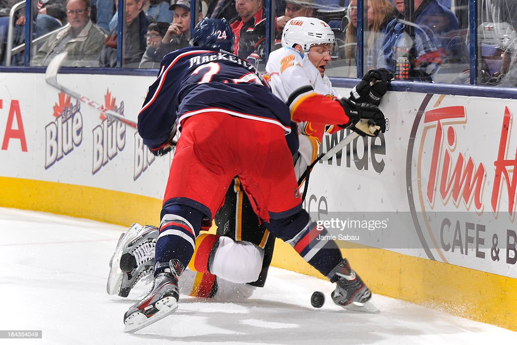 Derek Smith #27 of the Calgary Flames is checked off the puck by Derek MacKenzie #24 of the Columbus Blue Jackets during the third period on March 22, 2013 at Nationwide Arena in Columbus, Ohio. Columbus defeated Calgary 5-1.