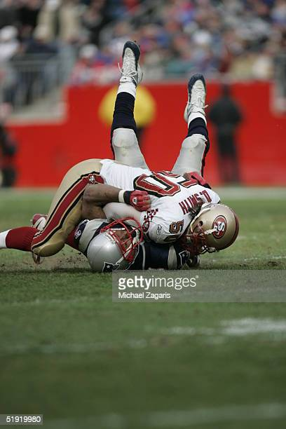 Derek Smith of the San Francisco 49ers sacks Josh Miller of the New England Patriots at Gillette Stadium on January 2 2004 in Foxborough...