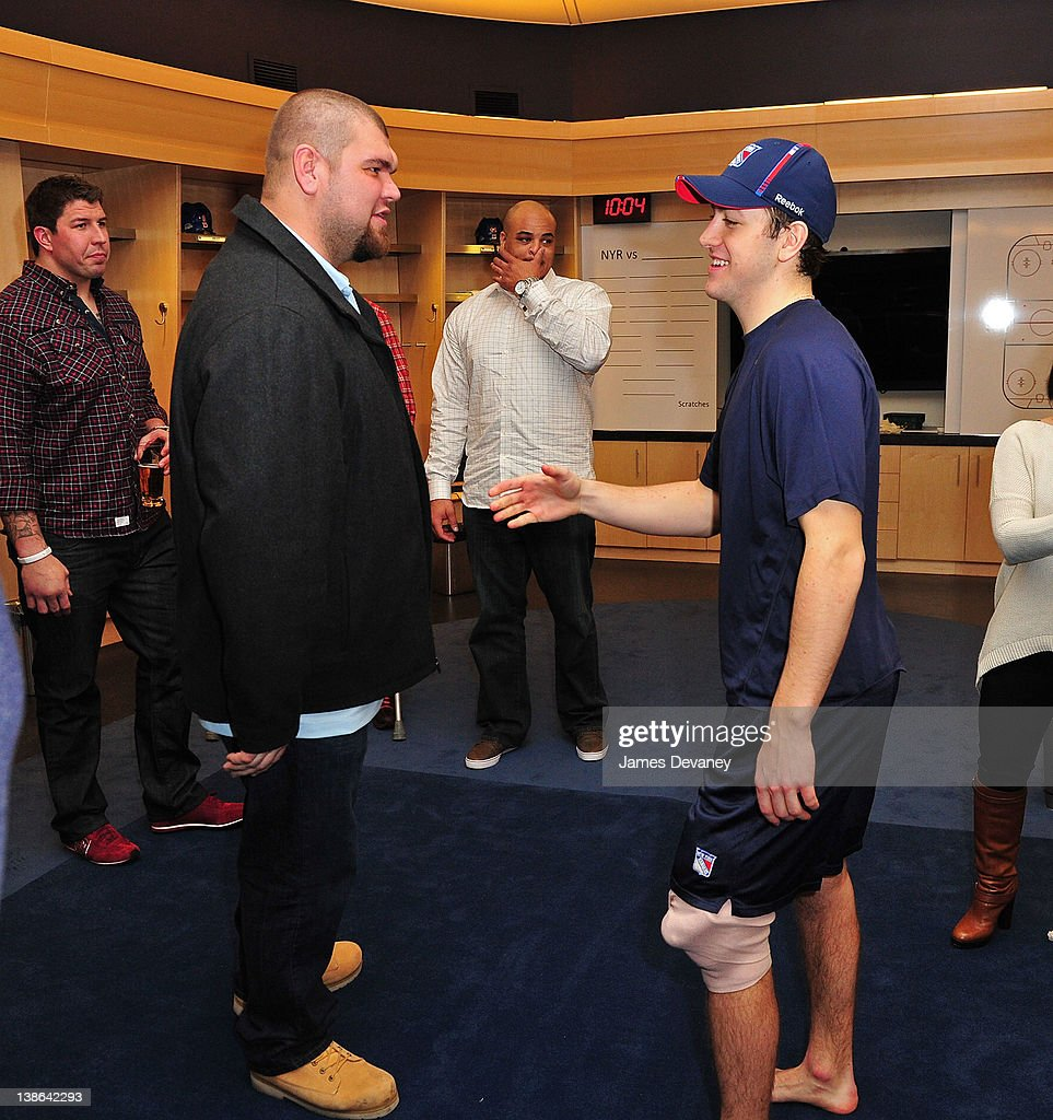 Derek Stepan (R) greets New York Giants players in the Rangers locker room after the Tampa Bay Lightning vs the New York Rangers game at Madison Square Garden on February 9, 2012 in New York City.