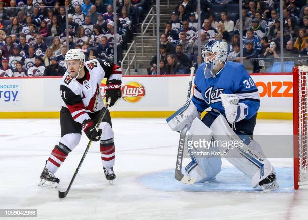 Derek Stepan of the Arizona Coyotes and goaltender Laurent Brossoit of the Winnipeg Jets keep an eye on the play during first period action at the...
