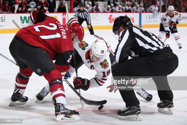 Derek Stepan of the Arizona Coyotes and Jonathan Toews of the Chicago Blackhawks face-off during the third period of the NHL game at Gila River Arena...