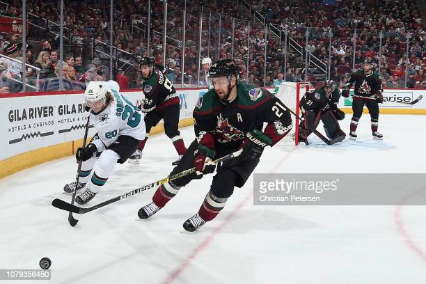 Derek Stepan of the Arizona Coyotes and Marcus Sorensen of the San Jose Sharks skate after a loose puck during the second period of the NHL game at...