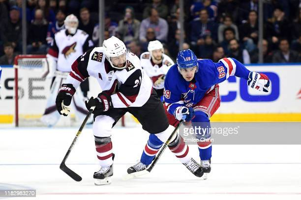 Derek Stepan of the Arizona Coyotes and Pavel Buchnevich of the New York Rangers race down the ice during their game at Madison Square Garden on...