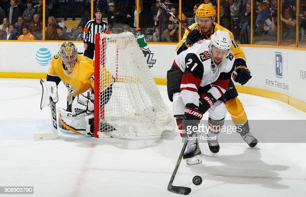 Derek Stepan of the Arizona Coyotes battles for the puck against Colton Sissons of the Nashville Predators as goalie Pekka Rinne of the Nashville...