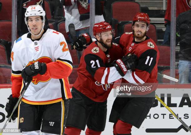 Derek Stepan of the Arizona Coyotes celebrates with teammate Brendan Perlini after scoring a goal as Travis Hamonic of the Calgary Flames skates off...
