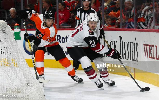 Derek Stepan of the Arizona Coyotes controls the puck behind the net while being pursued by Taylor Leier of the Philadelphia Flyers on October 30...