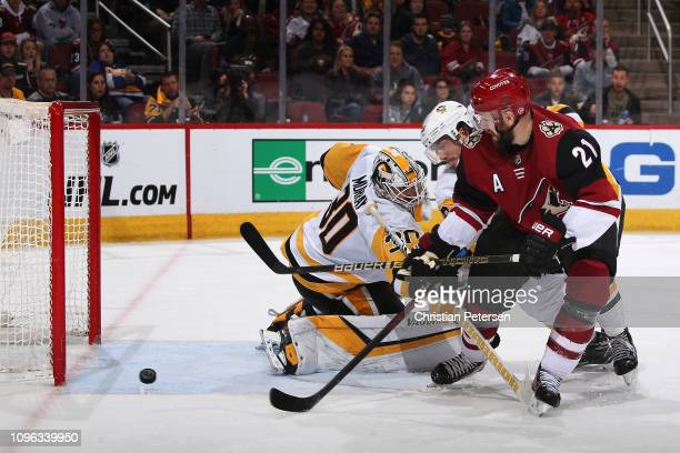 Derek Stepan of the Arizona Coyotes scores the game tying goal past goaltender Matt Murray and Kris Letang of the Pittsburgh Penguins during the...