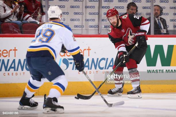 Derek Stepan of the Arizona Coyotes skates with the puck against Vince Dunn of the St Louis Blues during the first period of the NHL game at Gila...