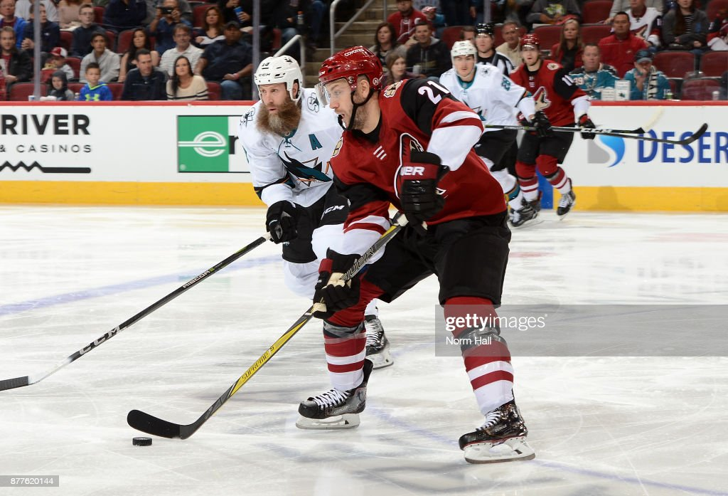 Derek Stepan #21 of the Arizona Coyotes skates with the puck ahead of Joe Thornton #19 of the San Jose Sharks during the first period at Gila River Arena on November 22, 2017 in Glendale, Arizona.