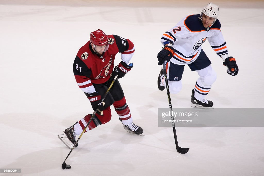 Derek Stepan #21 of the Arizona Coyotes skates with the puck ahead of Andrej Sekera #2 of the Edmonton Oilers during the first period of the NHL game at Gila River Arena on January 12, 2018 in Glendale, Arizona.