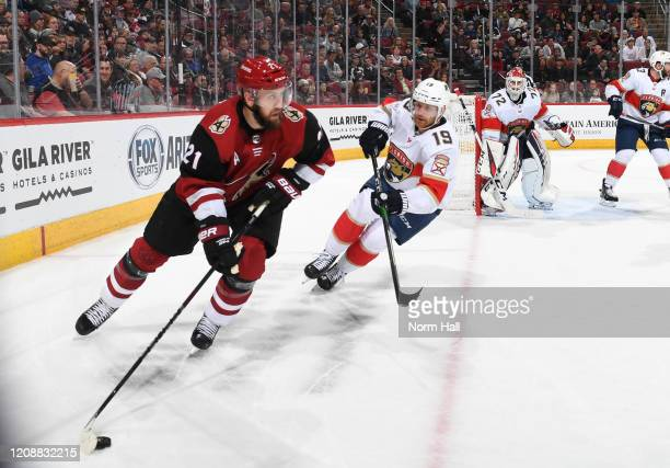 Derek Stepan of the Arizona Coyotes skates with the puck while being defended by Mike Matheson of the Florida Panthers at Gila River Arena on...