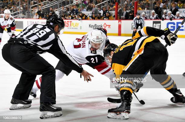 Derek Stepan of the Arizona Coyotes takes a faceoff against Riley Sheahan of the Pittsburgh Penguins at PPG Paints Arena on November 10 2018 in...